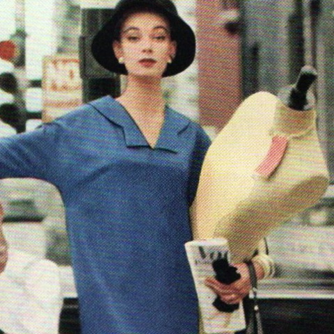 A woman hails a cab while holding a dress form and 1950s Vogue Pattern Book