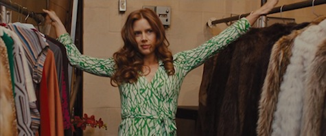 Amy Adams wears a green and white DVF wrap dress in American Hustle