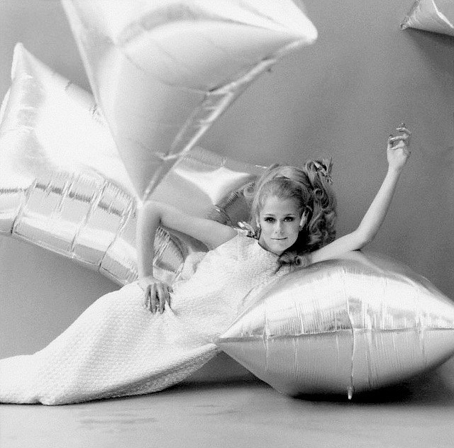 Model reclines on a large Andy Warhol silver helium-filled pillow wearing a Vogue Pattern 6928 dress
